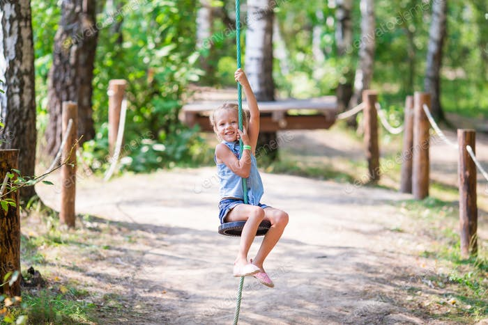 Adorable little girl having fun on a swing outdoors