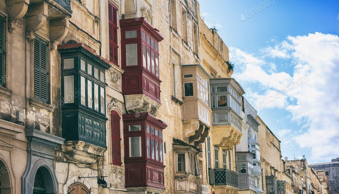 Malta, Valletta, building facade with covered balconies, with blue sky background, perspective view