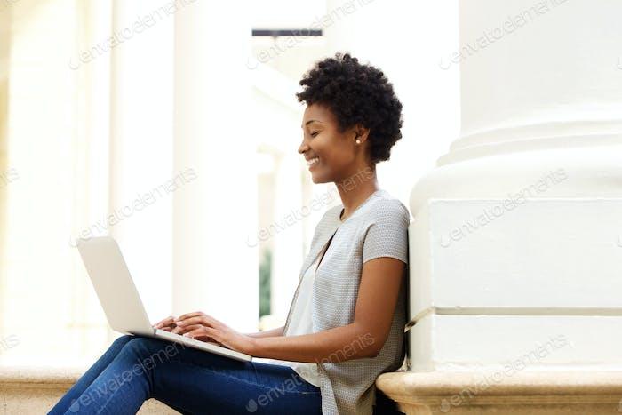 Junge afrikanische Frau sitzen außerhalb mit Laptop