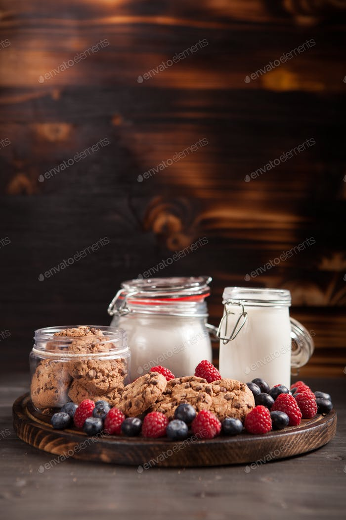 Freshly baked oatmeal biscuits with chocolate on wooden cutting board