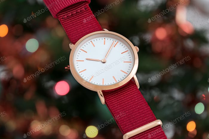 Red nylon strap wrist watch in front of Christmas lights