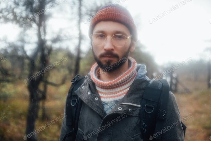 Blurred photography of bearded guy with glasses in forest