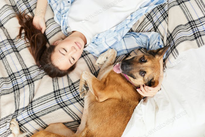 Asian Woman Lying on Bed with Dog