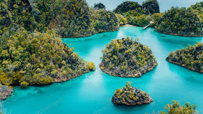 Pianemo Islands, Blue Lagoon with Green karst limestone Rocks, Raja Ampat, West Papua. Indonesia