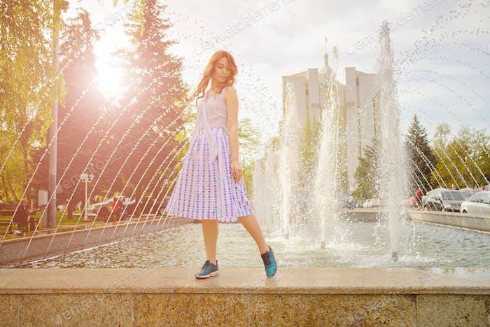 Dreamy girl by fountain