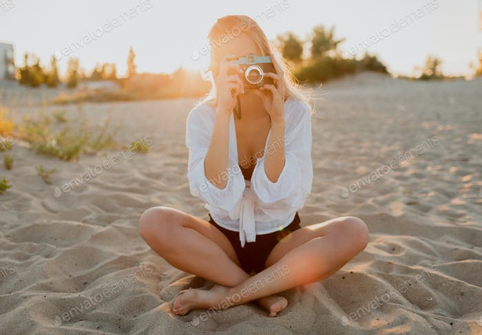Woman in white blouse sitting on the sand.