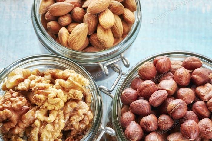 Walnuts, hazelnuts and almonds in jars.