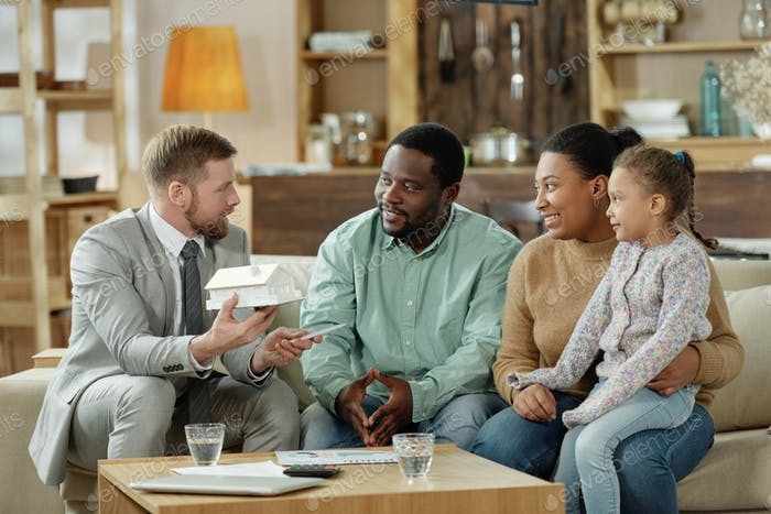 Adult counselor talking to ethnic family at home