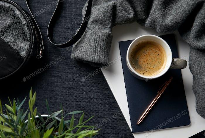 Flache Lay Lifestyle Shot mit Jumper Notizbuch und Handtasche auf schwarzem Hintergrund