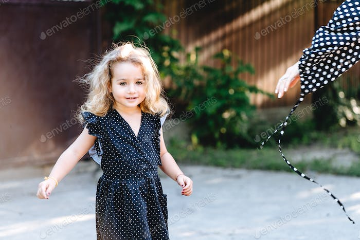 Little girl with curly hair posing at the camera