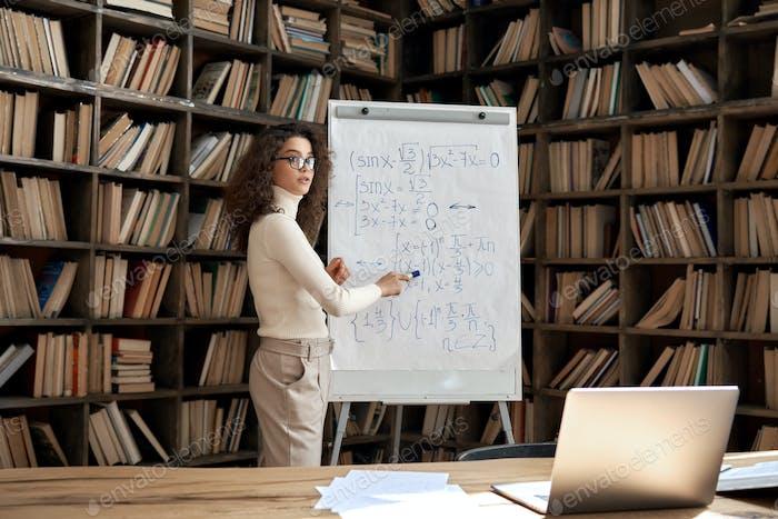 Joven mujer hispana tutora enseñando clase de matemáticas explicando la lección del curso remoto.