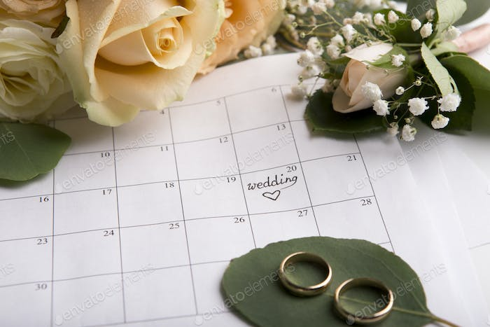 Creative flat lay of two golden rings with date choosing