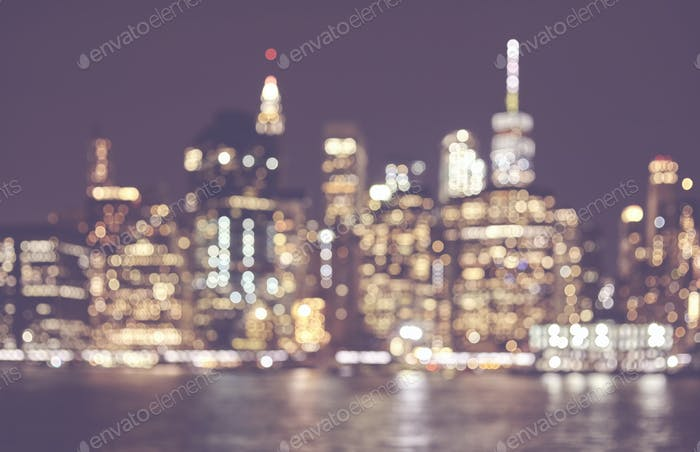 Blurred retro toned picture of Manhattan skyline at night, NYC.