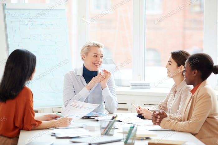 Group of Smiling Businesswomen at Meeting Table