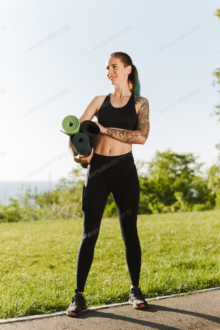 Young smiling lady in black sporty top and leggings standing with yoga mats in hands