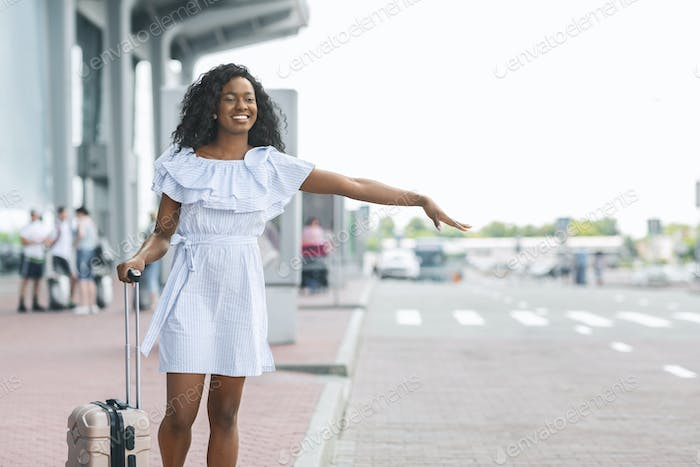 Young african woman waving hand near airport building