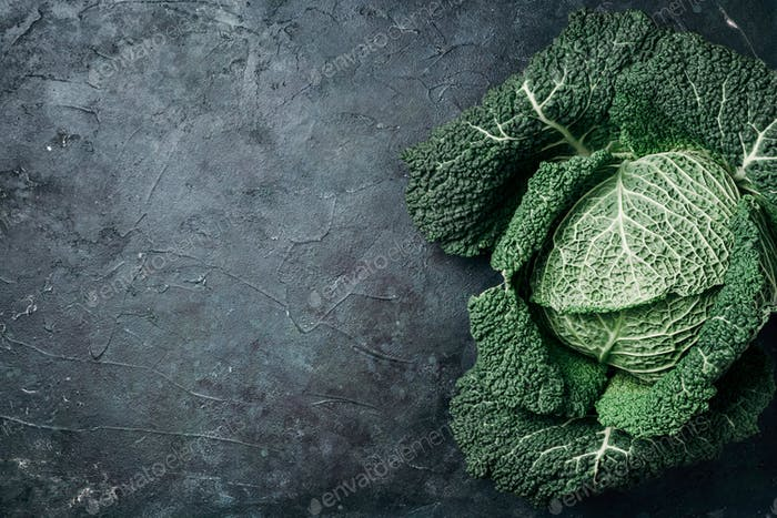 Raw green cabbage texture. Organic savoy cabbage on dark background. Top view. Copy space. Vegan and