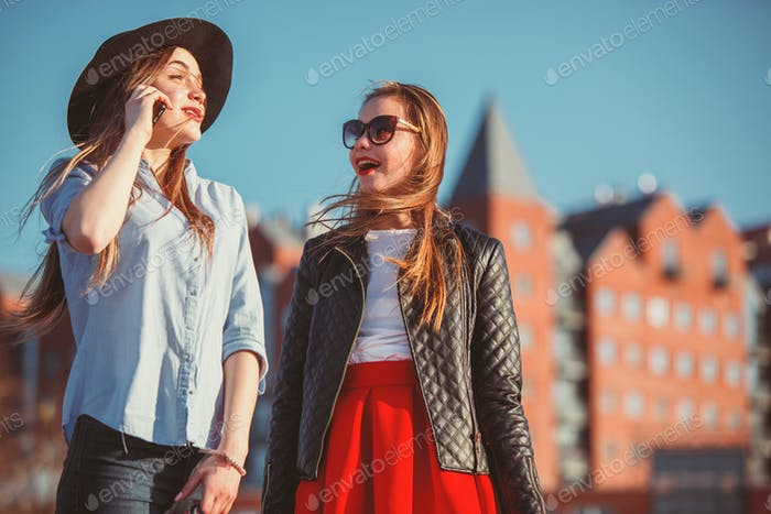 Two girls walking with shopping on city streets