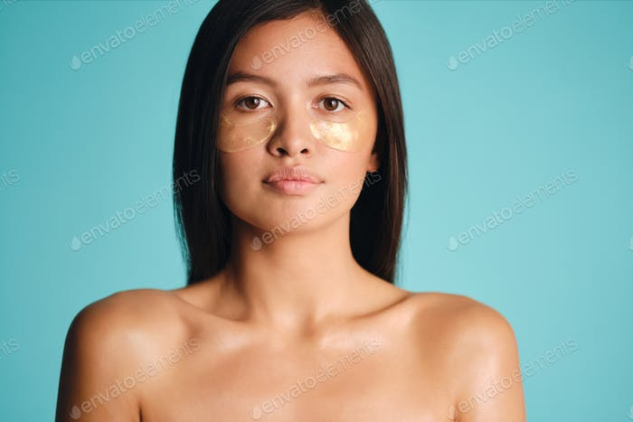 Beautiful Asian brunette girl with patches under eyes confidently looking in camera