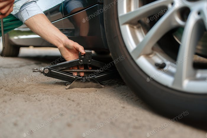 Car breakdown, male person repairing flat tyre