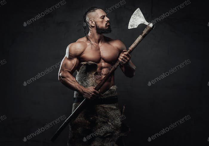 Viking fighter posing looking at his axe in dark background