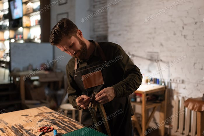 Bearded craftsman assembling equipment in leather workshop