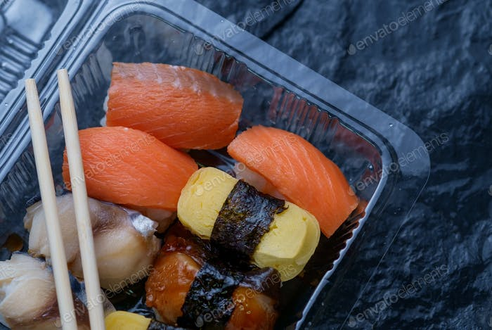 Sushi in the take-out box with chopsticks