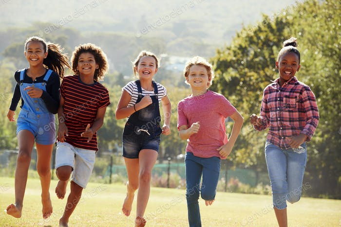 Six pre-teen friends running in a park, front view, close up