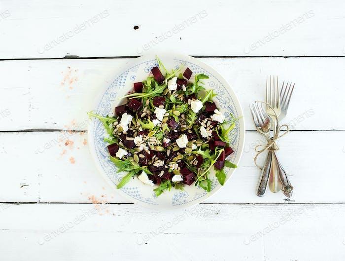 Beetroot salad with arugula, feta cheese, red salt and pumpkin seeds in vintage plate
