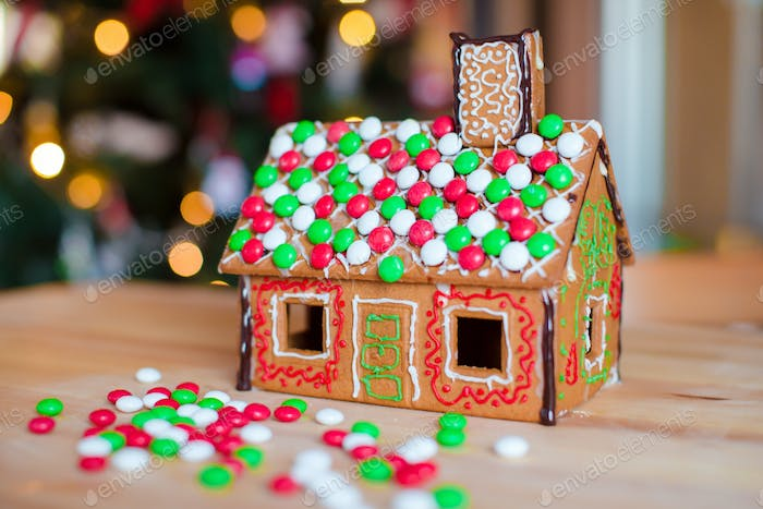 Gingerbread house decorated with colorful candies background Christmas tree lights
