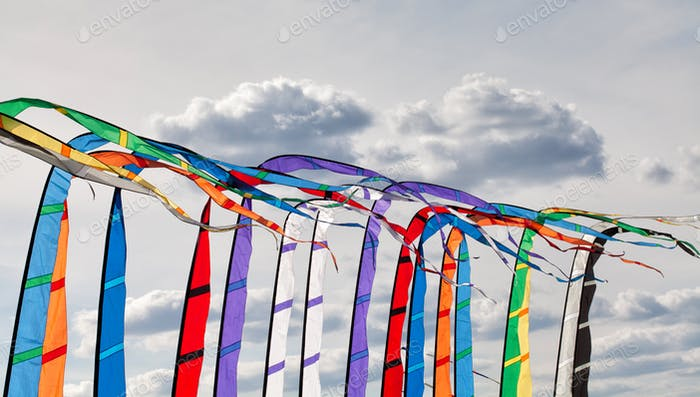 Multicolored flags banners fluttering in the wind, summer cloudy sky background
