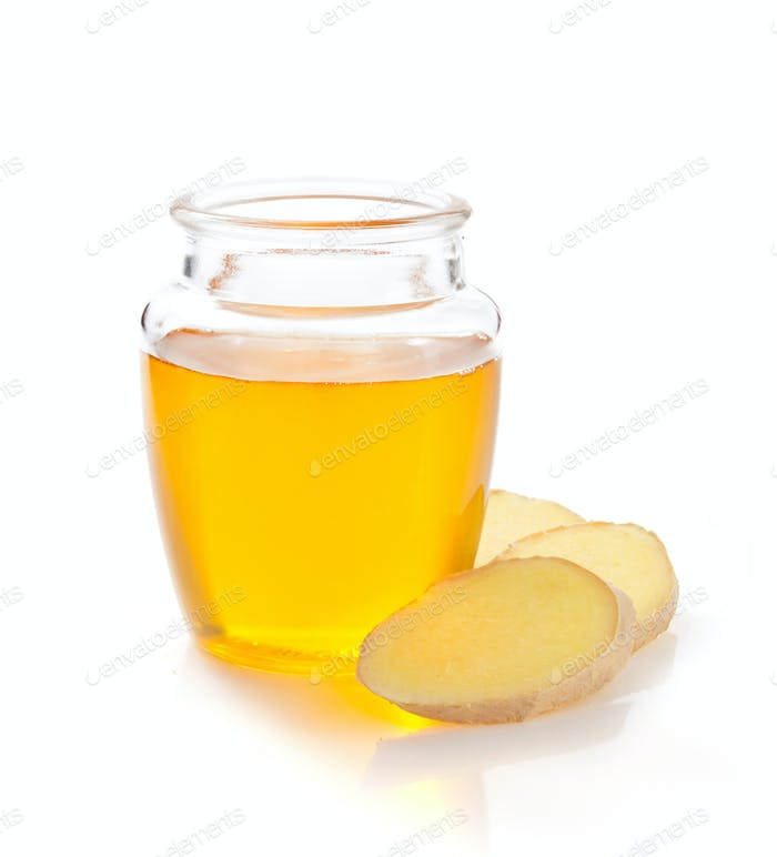 jar of honey and ginger on white background