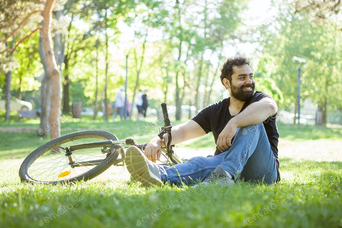 Man next to his bicycle resting on the grass