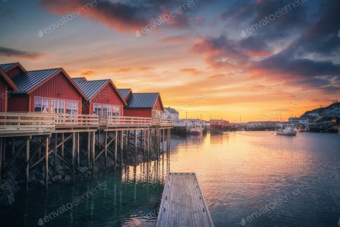 Red rorbu on wooden piles on sea coast, small jetty, colorful sky
