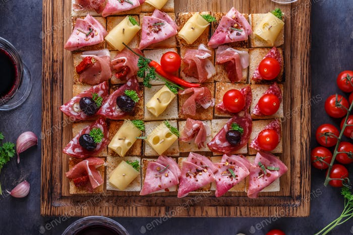 Close view of tiny bruschettas with prosciuto, ham and cheese
