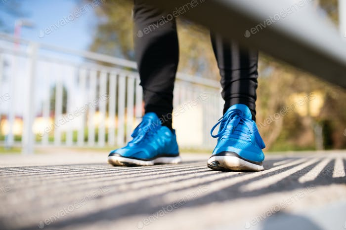 Legs of unrecognizable runner standing on concrete path, close u