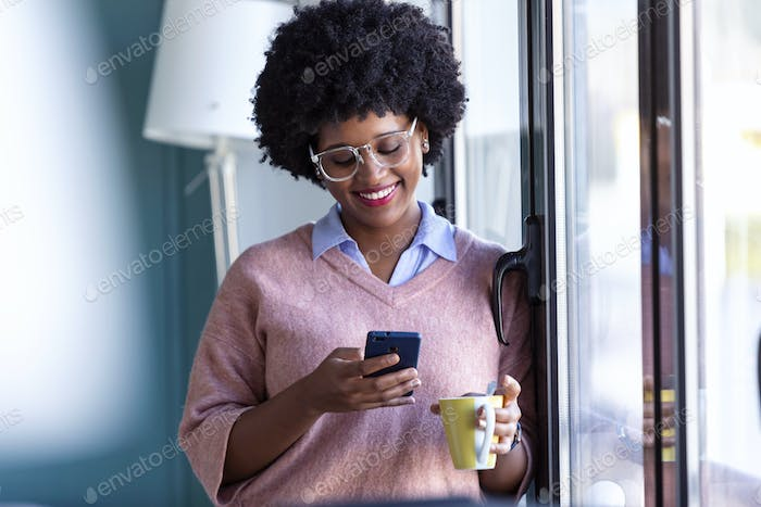 Hipster young businesswoman using her mobile phone while standing next to the window in the office.