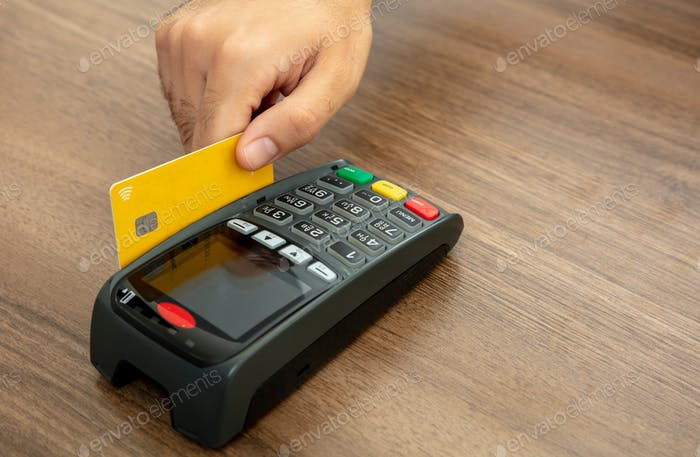Payment machine, POS terminal and credit card isolated on wooden background.