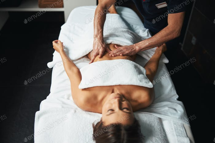 Unrecognized experienced massage therapist making manual therapy in wellness center