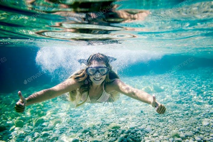 Schnorcheln im tropischen Meer, Frau zeigt Daumen-hoch-Zeichen unter Wasser