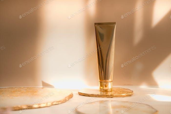 Goldene Kosmetikröhre auf Pastellfarbe Minimalismus Schönheit