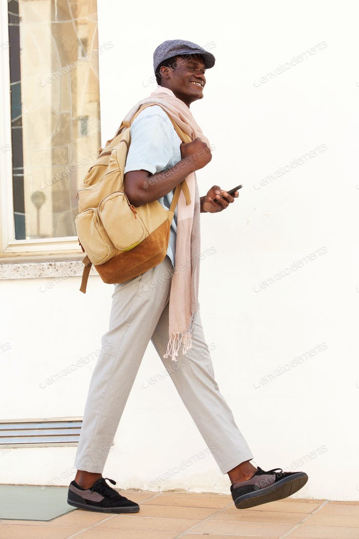 Full length handsome young guy walking with bag and phone