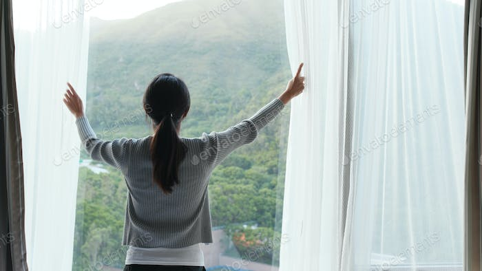 Woman unveil window curtain at morning