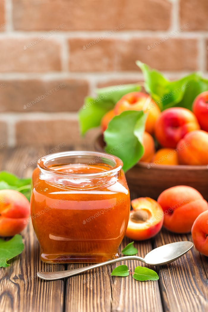 Apricot jam in a jar and fresh fruits with leaves