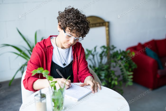 Young serious businesswoman sitting by table in cafe and making notes
