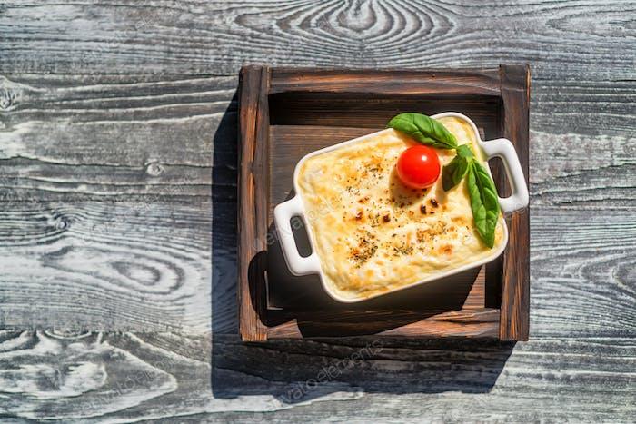 Tasty lasagna in baking dish on wooden board