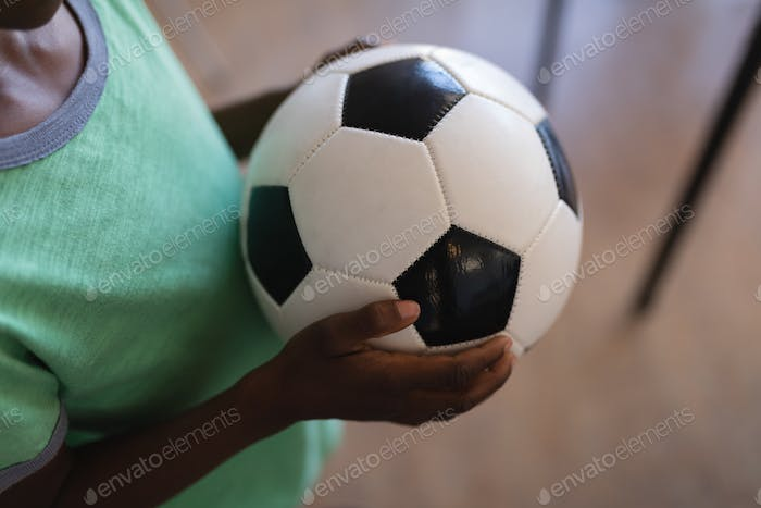 Mid section of schoolboy holding football in classroom of elementary school