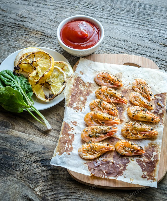 Shrimps with lemon and spicy sauce on the wooden background