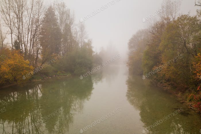 Autumn Fall landscape over foggy misty river
