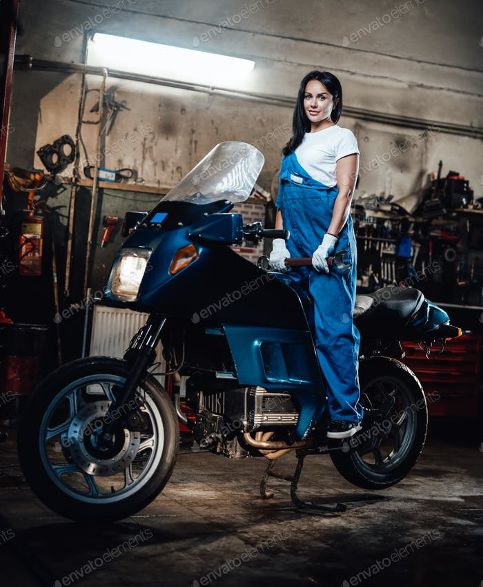Young female mechanic in blue overalls posing on sportbike in garage or workshop